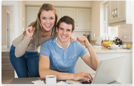 happy young couple at laptop computer